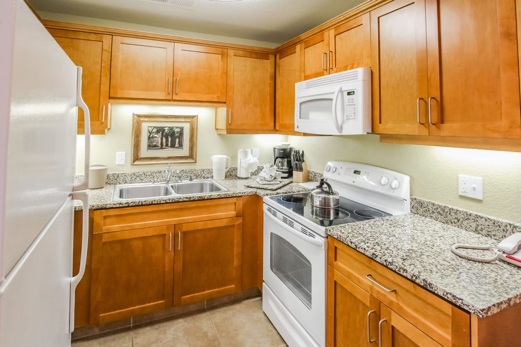 Photo of kitchen showcasing microwave oven, range/oven, double sinks, refrigerator, countertops and cabinets.