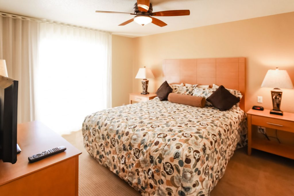 Photo of Bedroom Unit showcasing bed, side tables with lamps, ceiling fan, and side view of television.