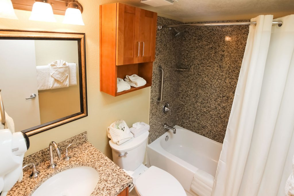 Photo bathroom with sink, toilet and bathtub/shower.